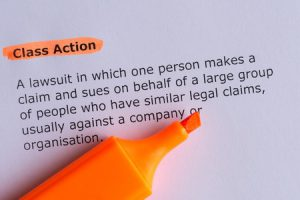 A piece of paper that says: Class Action | A lawsuit in which one person makes a claim and sues on behalf of a large group of people who have similar legal claims, usually against a company or organisation.