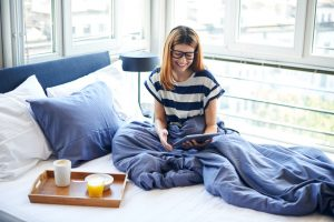 Woman sitting on a bed working