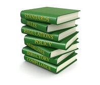 "Stack of books labeled ""Standards,"" ""Rules,"" ""Regulations,"" ""Policy,""""Guidelines,"" ""Directory,"" and ""Compliance"""